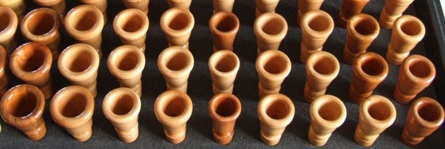 Display case showing a range of wooden Alphorn mouthpieces and plastic adaptor components for metal mouthpieces
